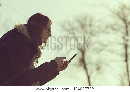 Girl in a park surfing the internet on a tablet