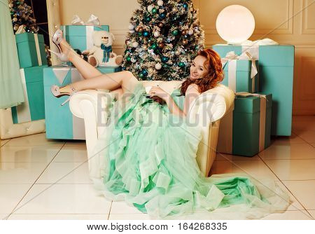 Young girl in green dress with Christmas tree