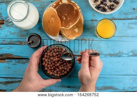 Woman Having Breakfast With Cereal Chocolate Balls