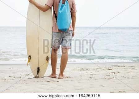 Cropped View Of Young Man With Blue Backpack Standing On Sandy Beach And Looking At Blue Sea Water,