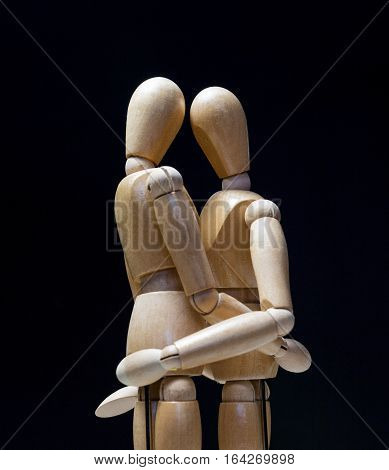 Wooden Mannequins-huggin close side 01 - Two wooden mannequins hugging with heads touching and arms around each other.