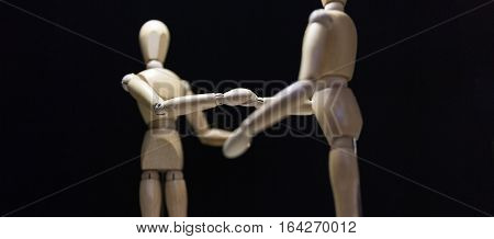 Wooden Mannequins-shaking-focusBlur - Two wooden mannequin's shaking hands. Shot close in with focus blur and from behind the right mannequin.