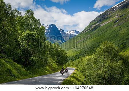 Empty road with mountain peaks on the horizon. Norwegian national travel route. Road to Trollstigen, Norway.