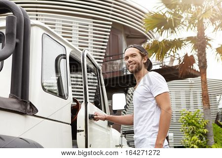 Outdoor Shot Of Young Caucasian Male Model With Beard Posing At His White Crossover Utility Vehicle,