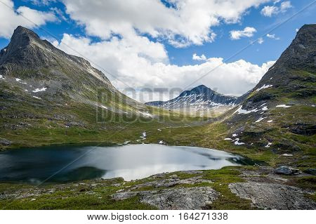 Lake from melted snow water in the mountain plateau on the Trollstigen road, Norway.