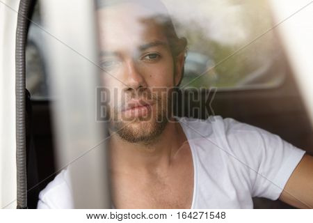 View From Window Glass Of Young Bearded Man In White T-shirt Looking Ahead At Road With Concentrated