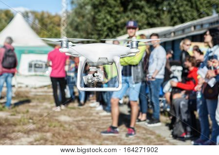 Man controls the copter. People stand around. Focus on the copter people blurred