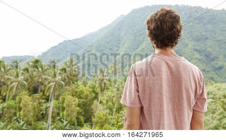 Rear View Of Caucasian Man In T-shirt Standing Outdoors In Front Of Rainforest And Contemplating Bea