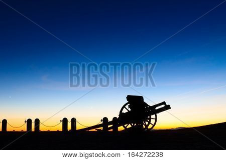 Cannon silhouette at twilight. Night landscape from Italian Alps.
