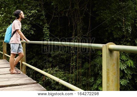 Adventure And Tourism. Handsome Caucasian Student Hiking In Rainforest. Young Hiker With Backpack St