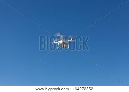 Quadrocopter unmanned camera hovers in bright blue sky