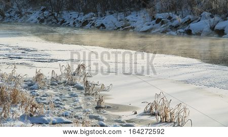 partly frozen river and vapour above its level in winter