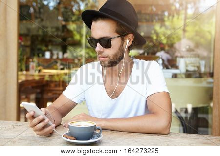 Fashionable Student Wearing Sunglasses And Black Hat Listening To Favourite Tracks On Earphones, Usi