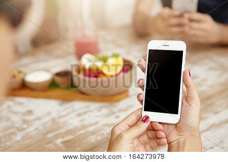 Elegant Female Hands With Neat Red Nails Using White Mobile Phone, Viewing Newsfeed Via Her Account