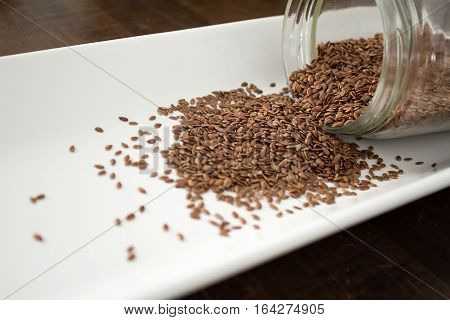 Flax Seeds Spilling Out Of Container On White Tray