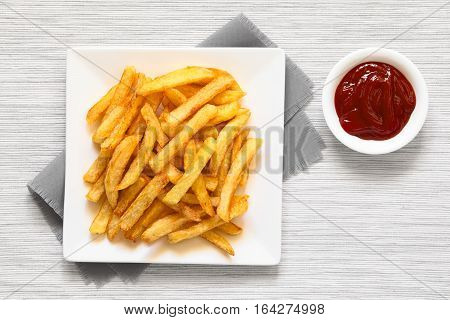 Fresh homemade crispy French fries on plate with a small bowl of ketchup on the side photographed overhead with natural light