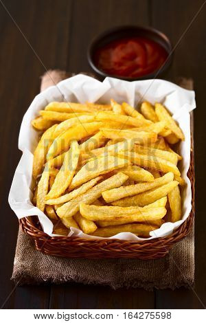 Fresh homemade crispy French fries in basket with a small bowl of ketchup in the back photographed with natural light (Selective Focus Focus in the middle of the image)