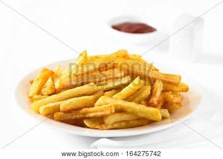 Fresh homemade crispy French fries on plate with a small bowl of ketchup and salt shaker in the back photographed with natural light (Selective Focus Focus in the middle of the image)