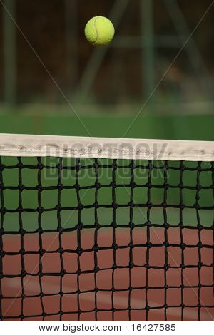 Tennis ball going over the net