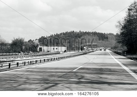 GERMANY - MAR 26 2016: German highway - Bundesautobahn or Federal Motorway highway with busy traffic on a spring day with beautiful green fields and blue clouds