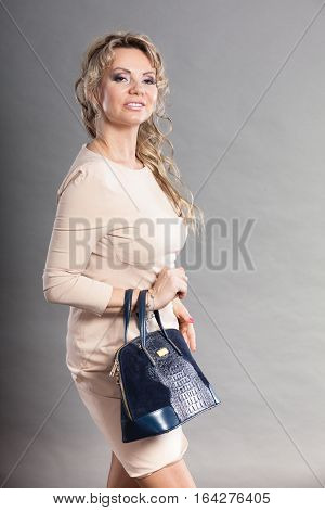 Fashion of women. Clothing and accessories. Mid aged blonde fashionable woman with deep blue handbag. Elegant lady on gray.