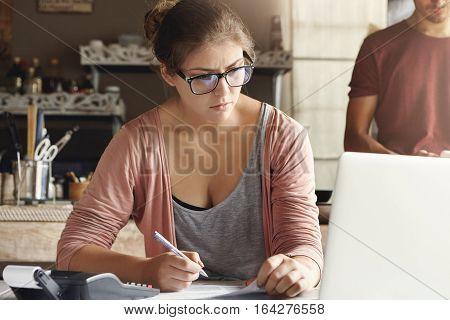 Young Married Couple Managing Family Budget, Reviewing Their Bank Accounts Using Notebook Computer A