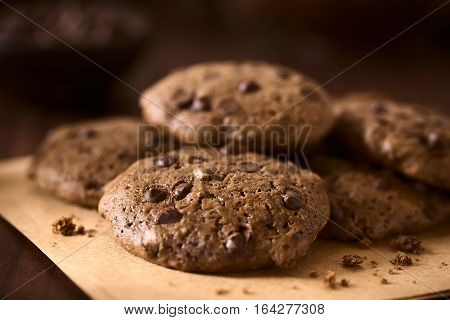 Homemade double chocolate chip cookies photographed on dark wood with natural light (Selective Focus Focus one third into the first cookie)