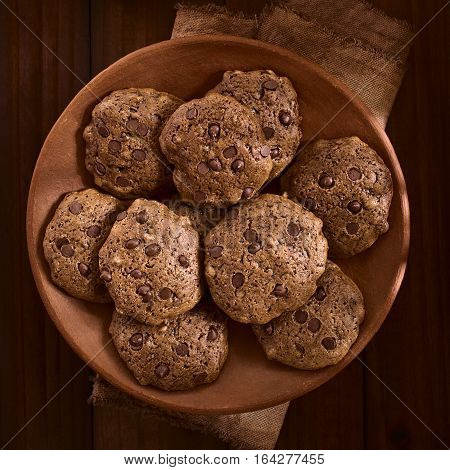 Homemade double chocolate chip cookies on rustic plate photographed overhead on dark wood with natural light