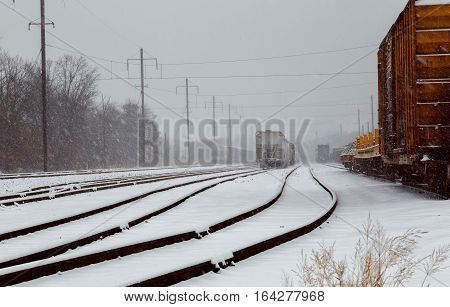 Back View Of Freight Train Running On The Railway Tracks In Winter While Is Snowing