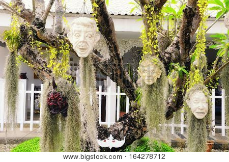 Sculpted stone heads hanging from a tree at wat rong khun white temple in chiang rai northern thailand.