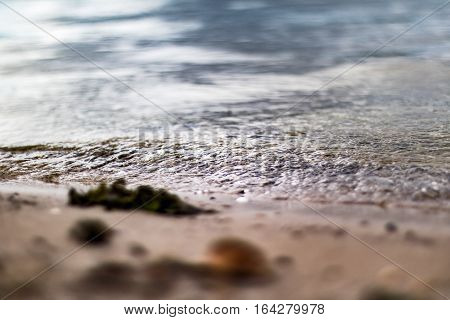 Extremely close up view of ripples washing up on the shore.