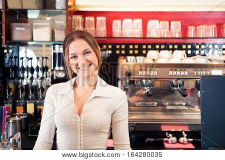 friendly bartender at a cafe, smiling at camera.