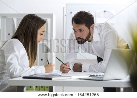 Portrait of a bearded man and a woman. They are working in a white office. He is looking at her and she is reading his notes