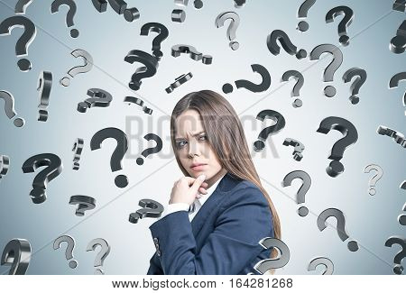 Portrait of a frowning woman in a business suit. She is plotting a suspicious action near a gray wall with falling question marks