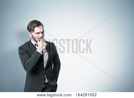 Pensive Businessman Near A Blue Wall