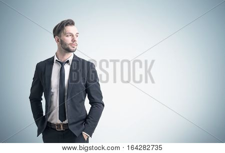 Confident Young Businessman Near A Gray Wall