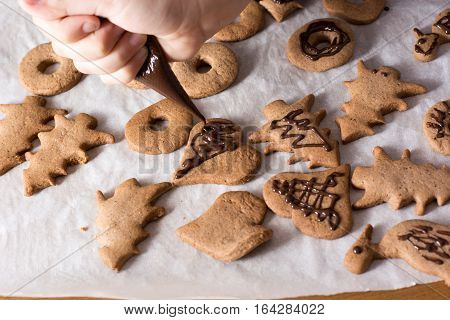 Boy Decorating Gingerbread Cookies With Chocolate