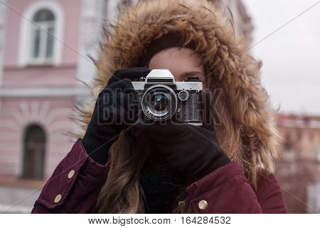 Hipster girl traveler with retro camera taking photo on city street at winter