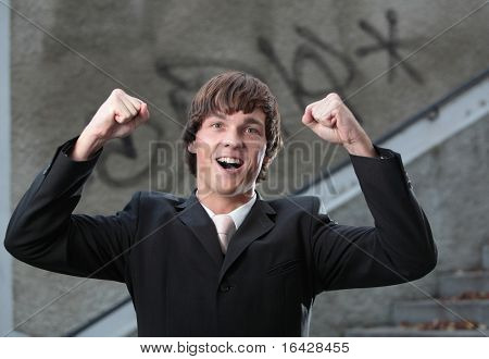 Portrait of a young handsome confident businessman exulting for joy after concluding a great business deal