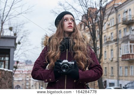 Hipster girl traveller with retro camera taking photos walking on city street