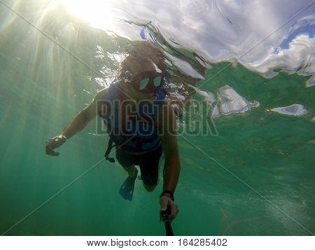 Boy diving snorkeling in the ocean underwater mask selfie
