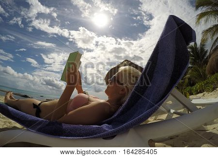 Mexico girl at beach chilling read book sun palm