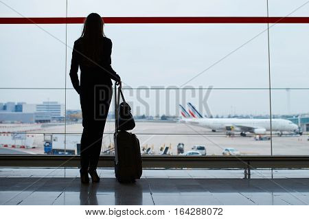 Silhouette of a young elegant business woman with hand luggage in international airport looking through the window at planes. Cabin crew member with suitcase. Travel concept poster