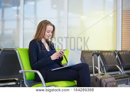 Woman In International Airport Terminal, Checking Her Phone