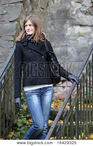 Portrait of a pretty young woman standing in a park on a small old staircase on cloudy autumn day