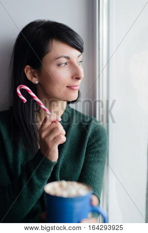 brunette young woman in green sweater sitting on window sill with cup of cocoa
