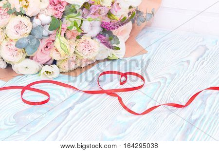 Valentine's Day. Valentine Gift. Red satin ribbon in Heart shape and bouquet of flowers on blue wooden background. Beautiful Valentine card art design