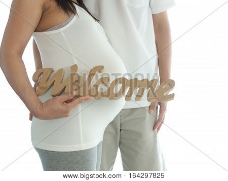 Pregnant woman with husband holding welcome message for incoming baby isolated on white background. Concept for baby shower and warm family.