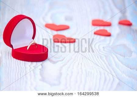 Ring for a marriage proposal and red hearts on wooden table. Romantic proposal wedding or Valentine's Day scene. Postcard for Valentine's day.