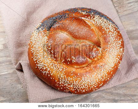 Wheat loaf with poppy seeds and sesame seeds on a old wooden table
